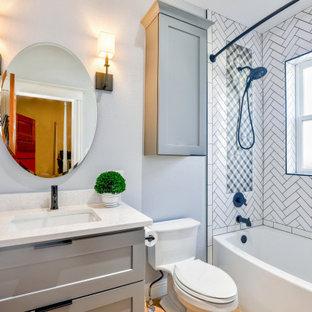 Mittelgroßes Shabby-Style Badezimmer mit Schrankfronten im Shaker-Stil, grauen Schränken, Einbaubadewanne, Duschbadewanne, weißen Fliesen, grauer Wandfarbe, hellem Holzboden, Unterbauwaschbecken, Quarzit-Waschtisch, Duschvorhang-Duschabtrennung, weißer Waschtischplatte, Einzelwaschbecken und freistehendem Waschtisch in Sonstige
