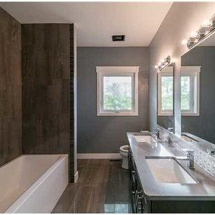 Modelo de cuarto de baño principal, actual, grande, con puertas de armario de madera en tonos medios, bañera empotrada, ducha esquinera, sanitario de dos piezas, paredes grises, suelo de madera pintada y lavabo bajoencimera