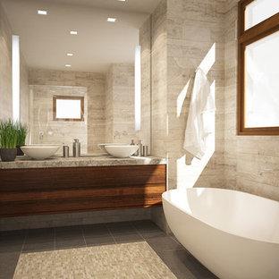 Diseño de cuarto de baño principal, minimalista, pequeño, con lavabo sobreencimera, armarios con paneles lisos, puertas de armario de madera oscura, encimera de piedra caliza, bañera exenta, baldosas y/o azulejos beige, baldosas y/o azulejos de piedra y paredes marrones