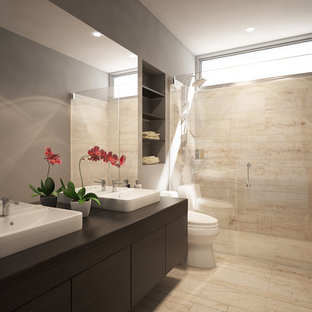 Inspiration for a small modern 3/4 beige tile and stone tile walk-in shower remodel in San Francisco with a vessel sink, flat-panel cabinets, dark wood cabinets, wood countertops, a one-piece toilet, brown walls and brown countertops