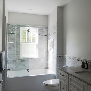 Mid-sized elegant master gray tile and stone tile marble floor and gray floor bathroom photo in New York with an undermount sink, furniture-like cabinets, white cabinets, solid surface countertops, a two-piece toilet, gray walls and a hinged shower door