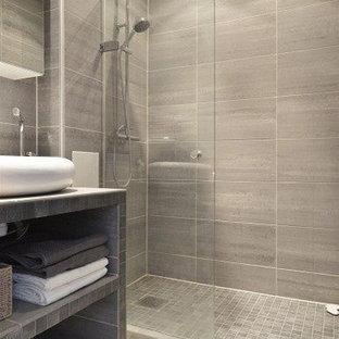 Immagine di una stanza da bagno con doccia minimalista di medie dimensioni con nessun'anta, ante grigie, doccia a filo pavimento, piastrelle grigie, pareti grigie, piastrelle in gres porcellanato, pavimento in gres porcellanato, lavabo a bacinella, top piastrellato, pavimento grigio e doccia aperta