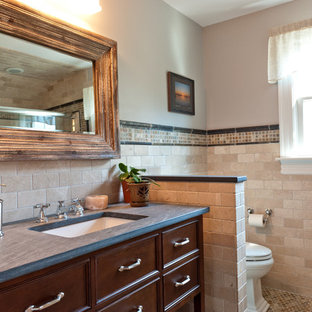 Inspiration for a mediterranean beige tile bathroom remodel in New York with raised-panel cabinets, brown cabinets, beige walls and an undermount sink