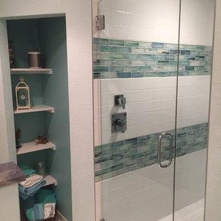 Immagine di una stanza da bagno padronale tropicale di medie dimensioni con doccia alcova, piastrelle blu e piastrelle di vetro
