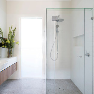This is an example of a mid-sized contemporary 3/4 bathroom in Melbourne with medium wood cabinets, white tile, porcelain tile, white walls, porcelain floors, engineered quartz benchtops, beige floor, flat-panel cabinets, a corner shower and a drop-in sink.