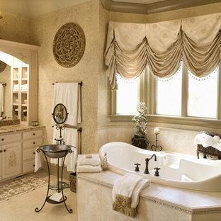 Ispirazione per un'ampia stanza da bagno padronale vittoriana con ante lisce, ante beige, vasca da incasso, piastrelle beige, pareti beige, lavabo sottopiano, top in granito e pavimento beige