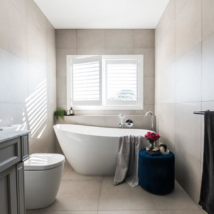 Design ideas for a mid-sized transitional master bathroom in Melbourne with recessed-panel cabinets, grey cabinets, a freestanding tub, a double shower, a one-piece toilet, porcelain tile, black walls, porcelain floors, an undermount sink, marble benchtops, grey floor and gray tile.