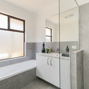 Design ideas for a mid-sized contemporary master bathroom in Perth with flat-panel cabinets, white cabinets, a drop-in tub, gray tile, white walls, an undermount sink, grey floor and beige benchtops.