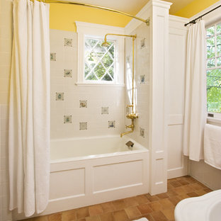 This is an example of a medium sized traditional family bathroom in New York with a pedestal sink, white cabinets, marble worktops, a built-in bath, a shower/bath combination, a one-piece toilet, multi-coloured tiles, yellow walls, terracotta flooring and recessed-panel cabinets.