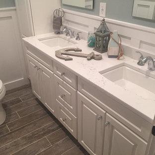 Foto på ett mellanstort vintage badrum med dusch, med luckor med upphöjd panel, vita skåp, ett badkar i en alkov, en dusch/badkar-kombination, en toalettstol med separat cisternkåpa, vit kakel, gröna väggar, klinkergolv i porslin, ett undermonterad handfat, bänkskiva i kvarts, grått golv och dusch med duschdraperi