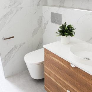 Imagen de cuarto de baño con ducha, minimalista, pequeño, con armarios con paneles lisos, puertas de armario con efecto envejecido, ducha abierta, sanitario de pared, baldosas y/o azulejos blancos, baldosas y/o azulejos de porcelana, paredes blancas, suelo de baldosas de porcelana, lavabo sobreencimera, encimera de cuarzo compacto, suelo gris, ducha abierta y encimeras blancas