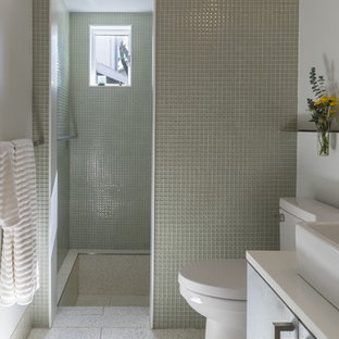 Bathroom - small modern master glass tile and green tile gray floor and terrazzo floor bathroom idea in Baltimore with a vessel sink, flat-panel cabinets, solid surface countertops, a one-piece toilet, white walls and gray cabinets