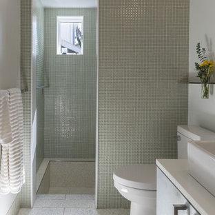 Immagine di una piccola stanza da bagno padronale moderna con lavabo a bacinella, ante lisce, top in superficie solida, doccia alcova, WC monopezzo, piastrelle di vetro, pareti bianche, ante grigie, piastrelle verdi, pavimento grigio, doccia aperta e pavimento alla veneziana