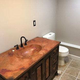 Diseño de cuarto de baño principal, de estilo americano, de tamaño medio, con armarios con paneles empotrados, puertas de armario de madera en tonos medios, ducha empotrada, sanitario de dos piezas, paredes beige, suelo de baldosas de cerámica, lavabo integrado, encimera de cobre, suelo beige y ducha abierta
