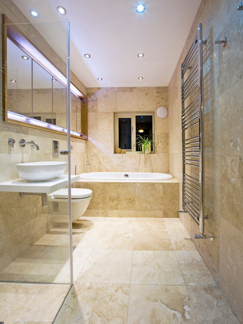Example of a mid-sized trendy travertine tile drop-in bathtub design in  Perth