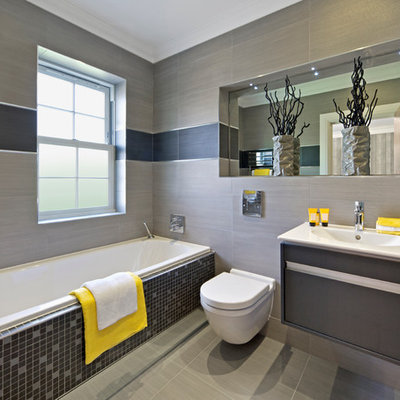 Example of a trendy gray tile drop-in bathtub design in Perth with an integrated sink, flat-panel cabinets, a wall-mount toilet and gray walls