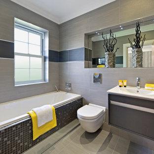 Ejemplo de cuarto de baño actual con lavabo integrado, armarios con paneles lisos, bañera encastrada, sanitario de pared, baldosas y/o azulejos grises y paredes grises