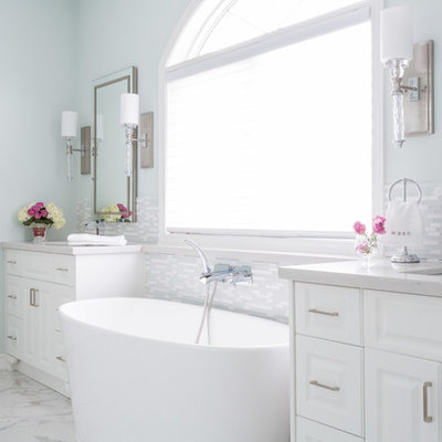 Inspiration for a large timeless master white tile and matchstick tile marble floor freestanding bathtub remodel in Toronto with raised-panel cabinets, an undermount sink, blue walls, white cabinets, a two-piece toilet and granite countertops