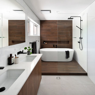 Inspiration for a contemporary bathroom in Perth with flat-panel cabinets, dark wood cabinets, a freestanding tub, brown tile, an undermount sink, grey floor and white benchtops.