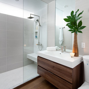 Example of a minimalist gray tile bathroom design in Toronto with an integrated sink, flat-panel cabinets and dark wood cabinets