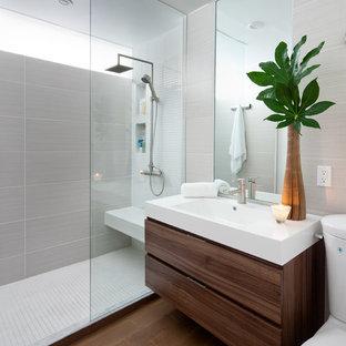 Ejemplo de cuarto de baño minimalista con lavabo integrado, armarios con paneles lisos, puertas de armario de madera en tonos medios, ducha abierta, baldosas y/o azulejos grises y ducha abierta