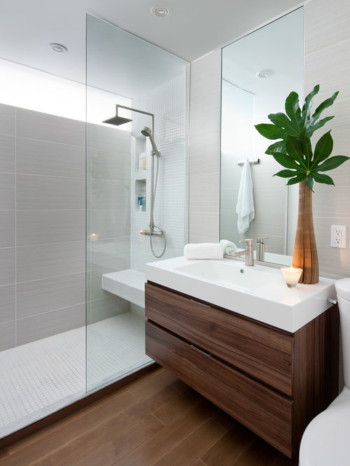 Example of a minimalist gray tile bathroom design in Toronto with an  integrated sink, flat