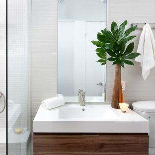 Imagen de cuarto de baño contemporáneo con lavabo integrado, puertas de armario de madera oscura, encimera de laminado, ducha abierta, sanitario de dos piezas, baldosas y/o azulejos beige, baldosas y/o azulejos de porcelana y armarios con paneles lisos