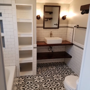 Small country master black and white tile and ceramic tile ceramic floor and black floor bathroom photo in St Louis with distressed cabinets, a two-piece toilet, gray walls, a vessel sink, wood countertops and brown countertops