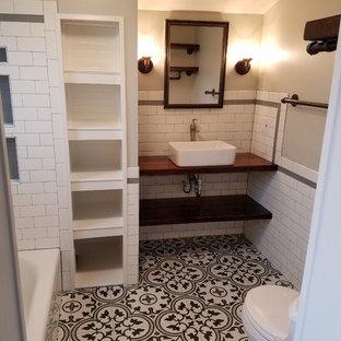 Idéer för små lantliga brunt en-suite badrum, med skåp i slitet trä, ett badkar i en alkov, en dusch/badkar-kombination, en toalettstol med separat cisternkåpa, svart och vit kakel, keramikplattor, grå väggar, klinkergolv i keramik, ett fristående handfat, träbänkskiva, svart golv och dusch med duschdraperi