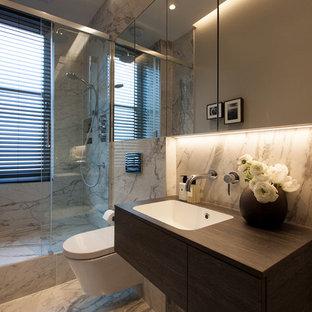 Foto di una piccola stanza da bagno con doccia minimal con ante marroni, doccia aperta, WC sospeso, piastrelle bianche, piastrelle di marmo, pareti grigie, pavimento in gres porcellanato, lavabo sospeso, top in laminato, pavimento bianco e porta doccia scorrevole