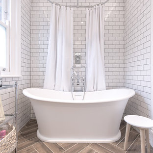 Traditional bathroom in Hertfordshire with a freestanding bath, white tiles, metro tiles and brown floors.