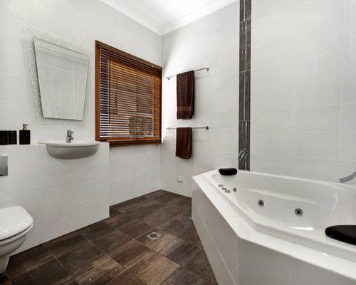 Modern bathroom idea in Sydney with tile countertops, a corner tub, an ...