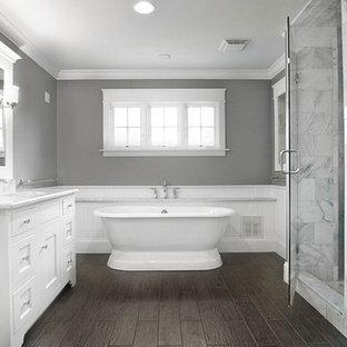Ejemplo de cuarto de baño principal, actual, grande, con lavabo bajoencimera, puertas de armario blancas, encimera de granito, ducha esquinera, baldosas y/o azulejos de vidrio, paredes grises, suelo de bambú, armarios con paneles empotrados y bañera exenta