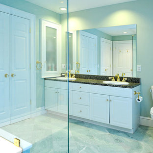 Example of a trendy green tile and stone tile corner shower design in Providence with a drop-in sink, raised-panel cabinets, white cabinets, granite countertops and a two-piece toilet