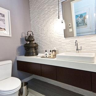 Ejemplo de cuarto de baño con ducha, de estilo zen, de tamaño medio, con armarios con paneles lisos, puertas de armario de madera en tonos medios, sanitario de dos piezas, baldosas y/o azulejos blancos, azulejos en listel, paredes grises, suelo laminado, lavabo de seno grande y suelo gris