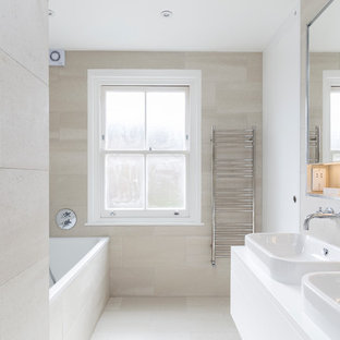 Inspiration for a small contemporary family bathroom in London with flat-panel cabinets, white cabinets, a built-in bath, a walk-in shower, a wall mounted toilet, beige tiles, porcelain tiles, beige walls, porcelain flooring, a built-in sink, quartz worktops, beige floors and a sliding door.
