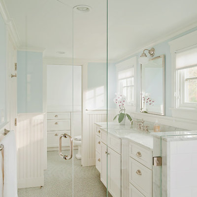 Example of a large classic master white tile and marble tile gray floor walk-in shower design in Providence with recessed-panel cabinets, white cabinets, blue walls, an undermount sink, marble countertops, a hinged shower door and gray countertops