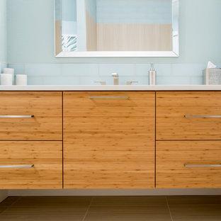Idee per una piccola stanza da bagno minimalista con ante lisce, ante in legno chiaro, piastrelle blu, piastrelle di vetro, pareti blu, pavimento con piastrelle in ceramica, lavabo sottopiano, top in quarzo composito e pavimento grigio