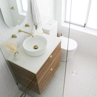 Modelo de cuarto de baño principal, minimalista, pequeño, con armarios con paneles lisos, puertas de armario de madera en tonos medios, ducha abierta, sanitario de una pieza, baldosas y/o azulejos blancos, baldosas y/o azulejos de pizarra, paredes blancas, suelo de baldosas de porcelana, lavabo sobreencimera, encimera de cuarzo compacto, suelo gris, ducha abierta y encimeras blancas
