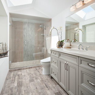 Inspiration for a mid-sized transitional master bathroom in Vancouver with an undermount sink, recessed-panel cabinets, grey cabinets, engineered quartz benchtops, an alcove shower, a bidet, gray tile, porcelain tile, porcelain floors, white walls, brown floor and a hinged shower door.