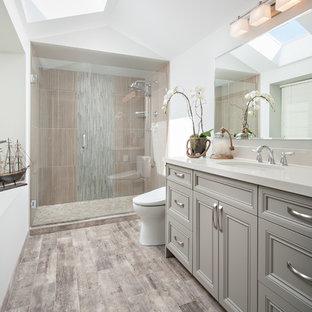 Aménagement d'une douche en alcôve principale classique de taille moyenne avec un lavabo encastré, un placard avec porte à panneau encastré, des portes de placard grises, un plan de toilette en quartz modifié, un bidet, un carrelage gris, des carreaux de porcelaine, un sol en carrelage de porcelaine, un mur blanc, un sol marron et une cabine de douche à porte battante.
