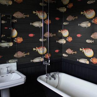 Ispirazione per una stanza da bagno per bambini bohémian di medie dimensioni con ante in stile shaker, ante nere, vasca con piedi a zampa di leone, vasca/doccia, lastra di vetro, pareti nere, pavimento in vinile, lavabo a colonna, top in marmo e pavimento nero