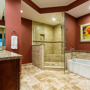 Photo of a large traditional master bathroom in Detroit with an undermount sink, shaker cabinets, an alcove tub, a corner shower, a two-piece toilet, medium wood cabinets, engineered quartz benchtops, multi-coloured tile, stone tile, red walls, travertine floors, beige floor and a hinged shower door.