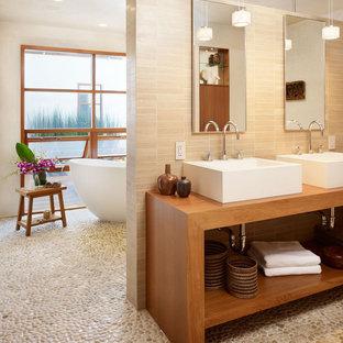 ロサンゼルスの中くらいのトロピカルスタイルのおしゃれなマスターバスルーム (置き型浴槽、ベッセル式洗面器、石タイル、玉石タイル、オープンシェルフ、濃色木目調キャビネット、洗い場付きシャワー、壁掛け式トイレ、ベージュのタイル、ベージュの壁、木製洗面台、マルチカラーの床、オープンシャワー、ブラウンの洗面カウンター) の写真