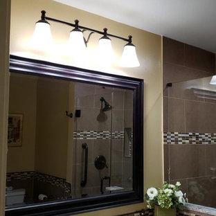 ヒューストンの中くらいのトラディショナルスタイルのおしゃれなマスターバスルーム (レイズドパネル扉のキャビネット、茶色いキャビネット、オープン型シャワー、分離型トイレ、茶色いタイル、磁器タイル、ベージュの壁、磁器タイルの床、アンダーカウンター洗面器、御影石の洗面台、ベージュの床、開き戸のシャワー、ベージュのカウンター) の写真