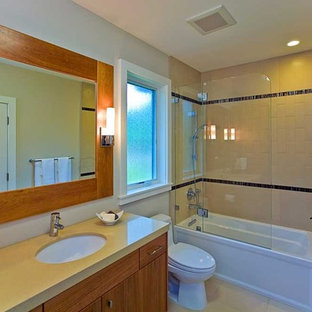 Example of a mid-sized trendy beige tile and porcelain tile porcelain floor bathroom design in San Francisco with an undermount sink, furniture-like cabinets, medium tone wood cabinets, solid surface countertops, a one-piece toilet and white walls