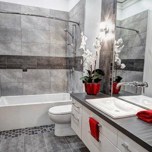 Réalisation d'une petit salle de bain design avec un lavabo posé, un placard à porte plane, un plan de toilette en stratifié, une baignoire en alcôve, un WC à poser, un carrelage gris, des carreaux de céramique, un mur gris, un sol en carrelage de céramique et des portes de placard blanches.