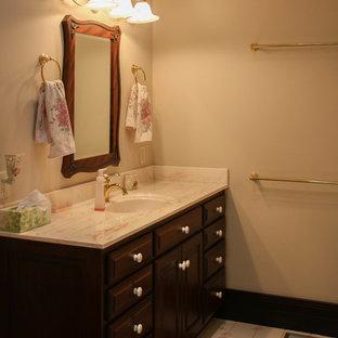 Foto di un'ampia stanza da bagno padronale stile rurale con ante con bugna sagomata, ante in legno bruno, pavimento in linoleum, top in marmo, pavimento bianco, pareti bianche e lavabo sottopiano