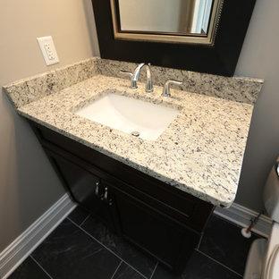 Aménagement d'une petit salle de bain craftsman avec un placard à porte plane, des portes de placard en bois sombre, un WC séparé, un carrelage gris, des carreaux de porcelaine, un mur gris, un sol en carrelage de porcelaine, un lavabo encastré, un plan de toilette en quartz, un sol noir et une cabine de douche avec un rideau.