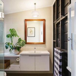 Удачное сочетание для дизайна помещения: детская ванная комната среднего размера в современном стиле с фасадами островного типа, фасадами цвета дерева среднего тона, угловым душем, унитазом-моноблоком, бежевой плиткой, керамической плиткой, черными стенами, полом из керамической плитки, монолитной раковиной, столешницей из искусственного камня, зеленым полом и душем с распашными дверями - самое интересное для вас